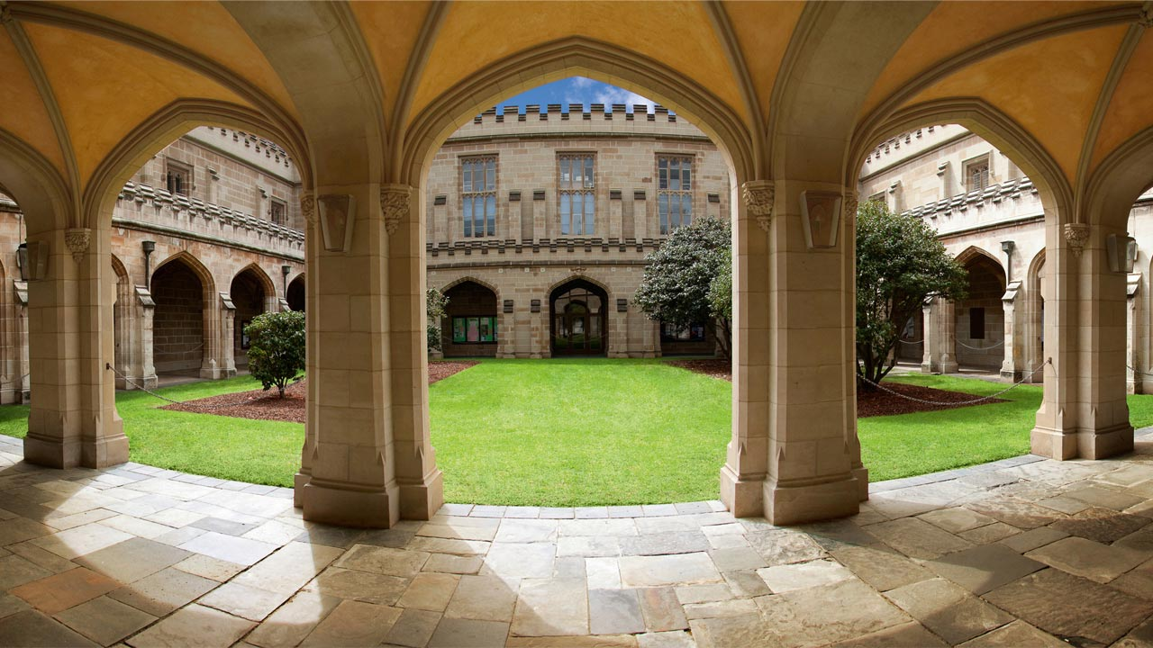 A vibrant green quad surrounded by a medieval-like corridor at University of Melbourne