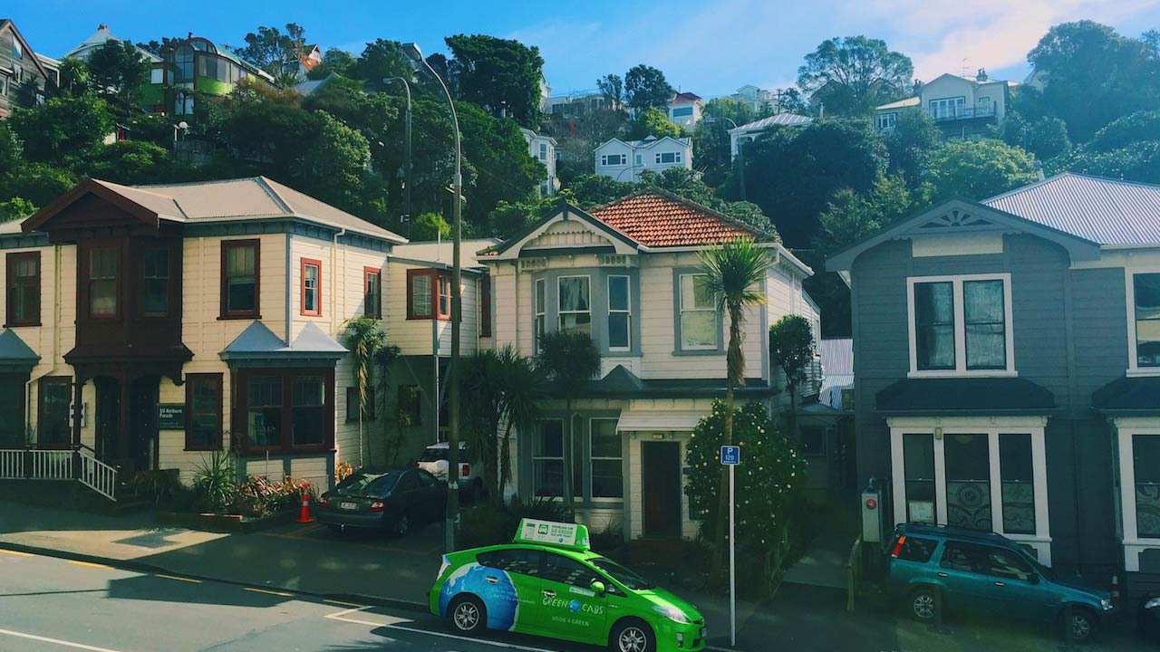 A green car parked in front of a row of houses in Wellington, New Zealand