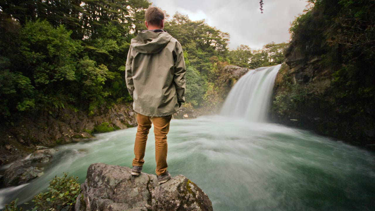 A man stands on a rock looking at a rushing waterfall near Wellington, New Zealand
