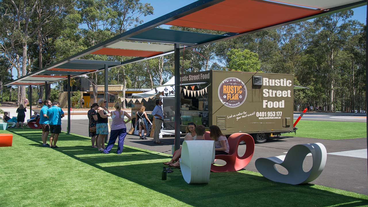 People gather outside a food truck on University of Newcastle's campus on a sunny day
