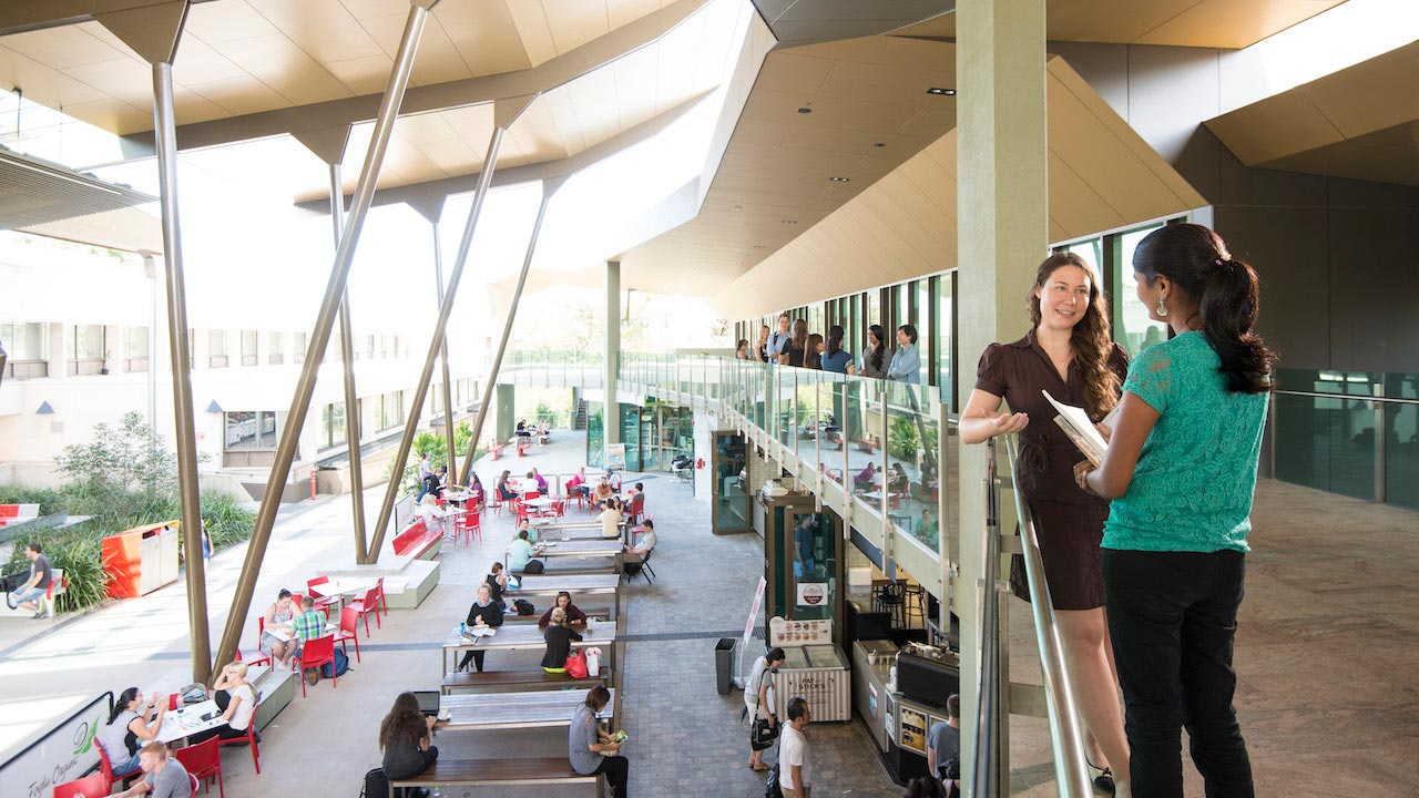 Two women stand conversing on Griffith Nathan Campus's open air common area