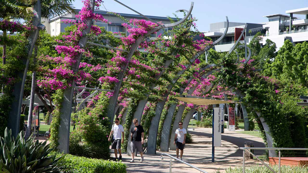 Three men walk along a flower covered walkway in Brisbane's Southbank