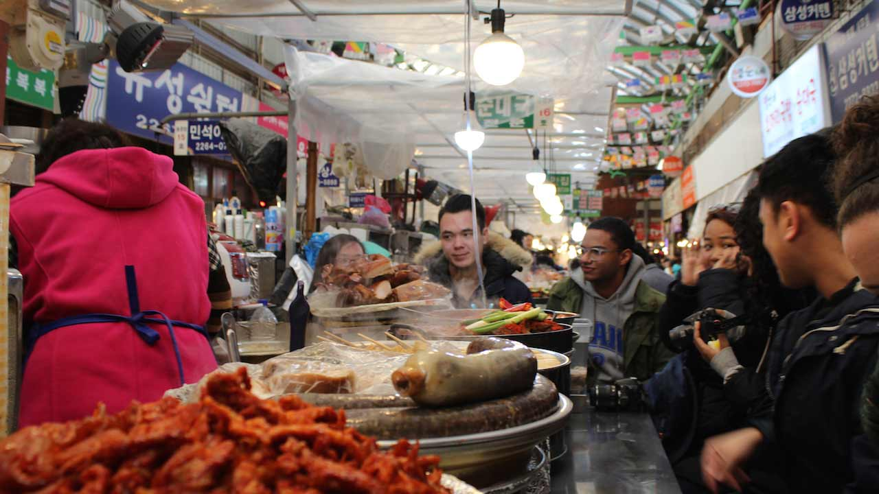 People stand around a stall inside a food court in Korea