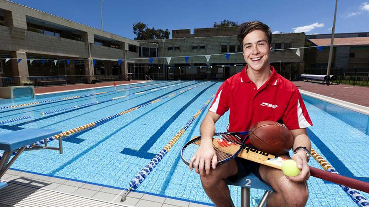 A man sits in front of an outdoor lap pool, smiling, holding an array of athletic gear