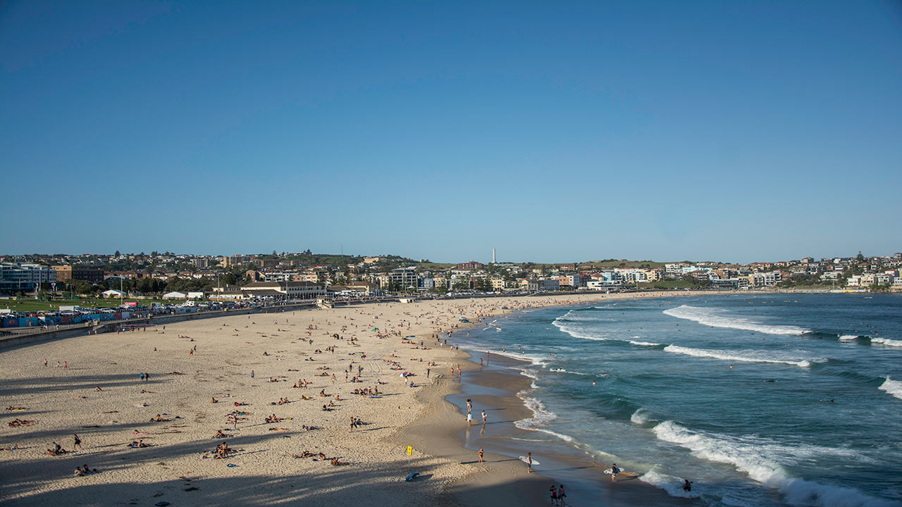 A landscape view of Bondi Beach in Sydney, as the waves come into the shore and many people lay about