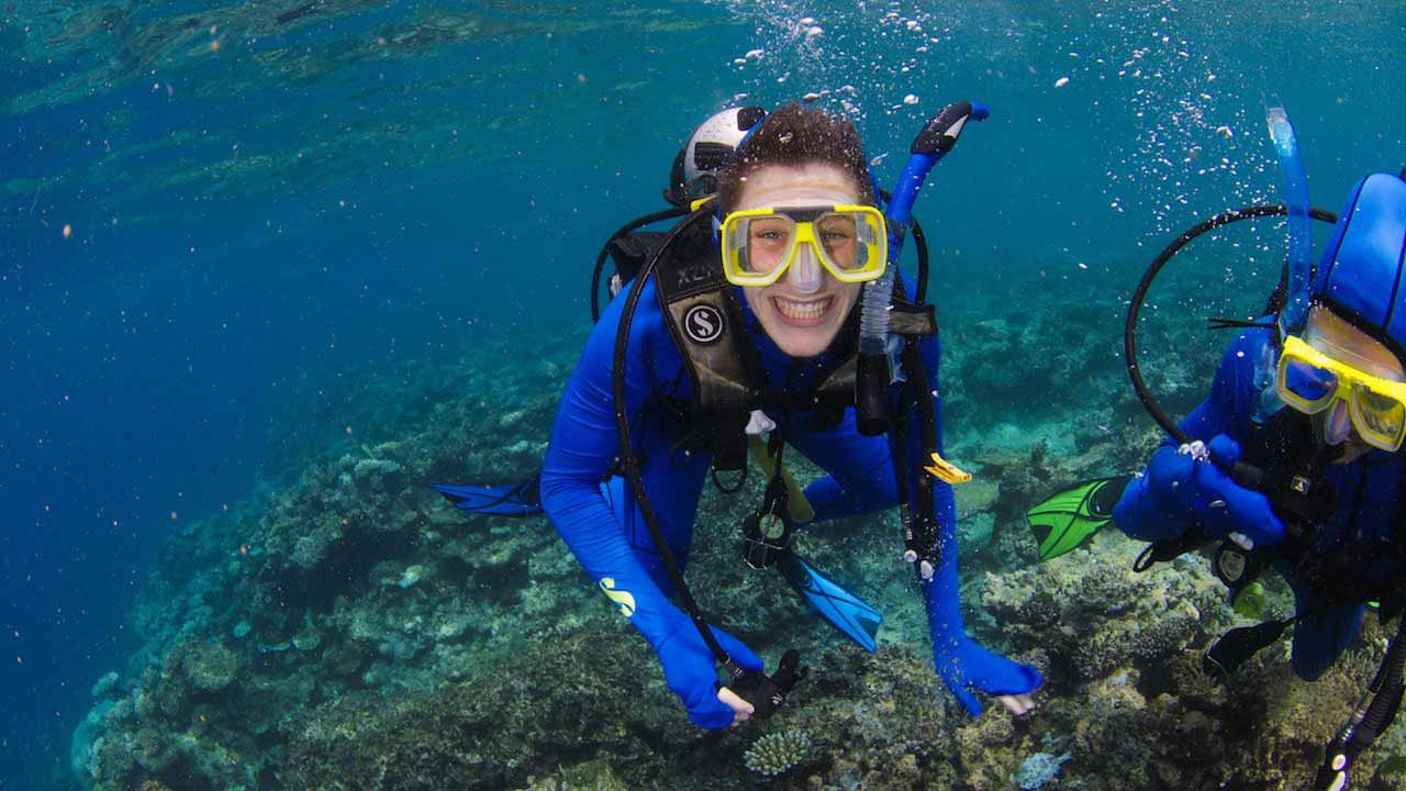A student smiles underwater while scuba diving in the Great Barrier Reef