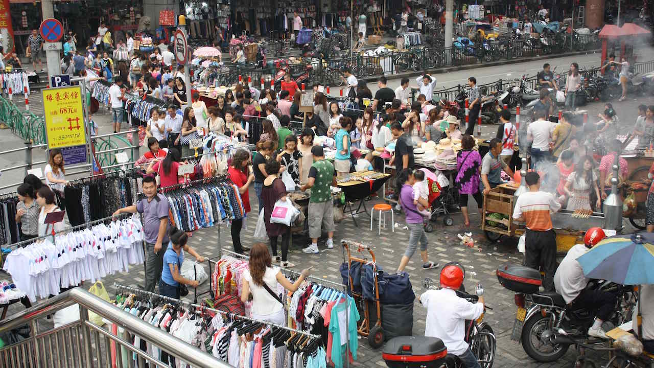 A crowded outdoor clothing market in Shanghai