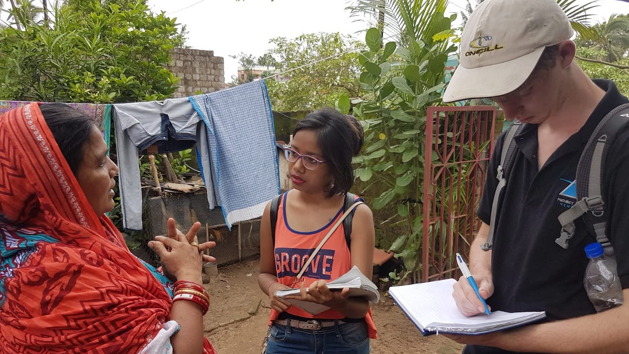 Interns taking notes conducting interview in India